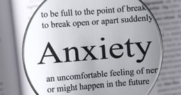 A photo of a magnifying glass enlarging the word anxiety in a dictionary which links to the talking cures contact page